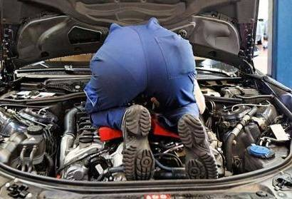 Car mechanic inspecting a bank repossessed vehicle